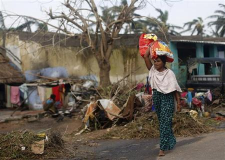 A woman carrying her belongings walks past partially damaged houses after Cyclone Phailin hit Gopalpur in Ganjam district in Odisha October 13, 2013. REUTERS/Ahmad Masood