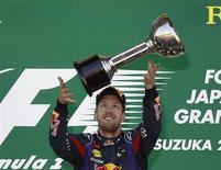 Piloto alemão da equipe Red Bull Sebastian Vettel brinca com troféu após vencer o Grande Prêmio do Japão de F1, no circuito de Suzuka. Vettel venceu o GP do Japão neste domingo, mas vai ter de esperar para conquistar seu quarto título mundial da Fórmula 1 depois que Fernando Alonso terminou a corrida em quarto. 13/10/2013. REUTERS/Toru Hanai