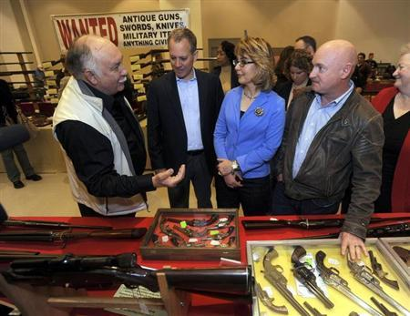 Show organizer Dave Petronis (L) leads (2nd L-R) New York Attorney General Eric Schneiderman, former U.S. Rep. Gabrielle Giffords, and her husband Mark Kelly on a tour of the New Eastcoast Arms Collectors Associates arms fair in Saratoga Springs, New York October 13, 2013. REUTERS/Tim Roske/Pool