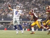 Oct 13, 2013; Arlington, TX, USA; Dallas Cowboys quarterback Tony Romo (9) throws a touchdown pass while being rushed by Washington Redskins inside linebacker Perry Riley (56) in the third quarter of the game at AT&T Stadium. Tim Heitman-USA TODAY Sports