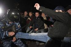 Протестующие дерутся с полицией в Бирюлево-Западное, Москва 13 октября 2013 года. Толпа протестующих устроила погромы и битву с ОМОНом на южной окраине Москвы после убийства молодого мужчины, ответственность за которое местные жители возложили на мигранта с Кавказа. REUTERS/Maxim Shemetov