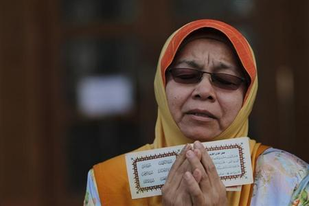 A Muslim woman recites a prayer during a demonstration outside Malaysia's Court of Appeal in Putrajaya, outside Kuala Lumpur October 14, 2013. REUTERS-Samsul Said