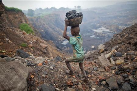A boy carries coal at an open cast coal field at Dhanbad district in Jharkhand September 20, 2012. REUTERS/Ahmad Masood/Files