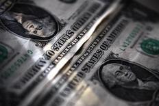 Долларовые купюры в банке в Торонто 26 марта 2008 года. Группа ТКС, в которую входит ТКС-банк Олега Тинькова, определил диапазон размещения GDR на акции компании в ходе IPO в $14 - 17,5, увеличив предполагаемый объем привлечения до $870 миллионов, не считая 15-процентного опциона на переподписку, говорится в сообщении компании. REUTERS/Mark Blinch
