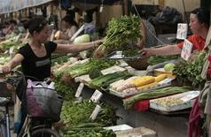 Женщина продает овощи на рынке в Наньцзине, провинция Цзянсу 10 июля 2008 года. Потребительская инфляция в Китае ускорилась в сентябре до 3,1 процента в годовом выражении, рекордного значения за семь месяцев, на фоне скачка цен на продовольствие из-за погодных условий, ограничивая возможности центробанка в поддержке экономики. REUTERS/Sean Yong