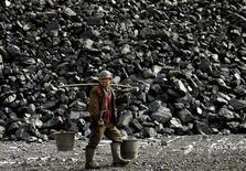 Китайский шахтёр у шахты в Датоне 22 февраля 2005 года. Уголь станет важнейшим в мировой экономике видом топлива вместо нефти к 2020 году, несмотря на усилия по сокращению выбросов углерода, прогнозирует консалтинговая фирма Wood Mackenzie. REUTERS/Reinhard Krause