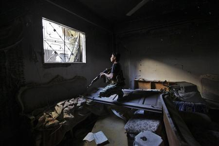 A Free Syrian army fighter carries his weapon in a damaged building in Jubaila neighbourhood in Deir al zor, eastern Syria October 13, 2013. REUTERS/Khalil Ashawi