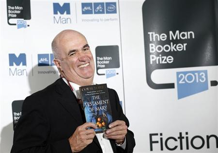 Man Booker Prize 2013 shortlist nominee Colm Toibin poses with his book ''The Testament of Mary'' during a photocall at the Southbank Centre in London, October 13, 2013. REUTERS/Olivia Harris