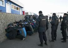 Российские полицейские задерживают гастарбайтеров в ходе рейда на овощебазу, попавшую в фокус внимания во время беспорядков в Москве. Фото от 14 октября 2013 года. По информации представителя столичной полиции Алексея Шапкина, около 1.200 человек задержаны в понедельник на овощном складе в Бирюлёво после волны беспорядков, вызванных гибелью молодого мужчины, ответственность за которое местные жители возложили на приезжего с Кавказа. REUTERS/Ivan Stolpnikov