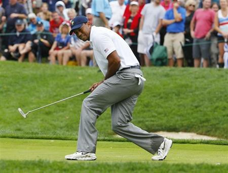 U.S. team member Tiger Woods misses a putt on the 14th green as he plays International member Richard Sterne of South Africa during the Singles matches for the 2013 Presidents Cup golf tournament at Muirfield Village Golf Club in Dublin, Ohio October 6, 2013. REUTERS/Jeff Haynes