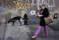 A woman walks past a new work by British graffiti artist Banksy on West 24th street in New York City in this file photo taken October 3, 2013. REUTERS/Mike Segar/Files