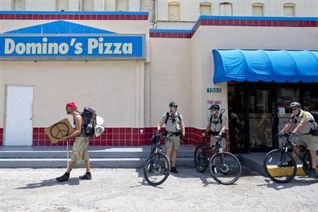 A protestor walks in front of a Domino's Pizza store during the Republican National Convention in Tampa, Florida August 30, 2012. REUTERS/Philip Andrews