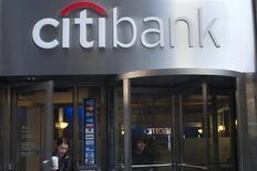 Люди выходят из отделения Citibank в Нью-Йорке 16 октября 2012 года. Скорректированная прибыль Citigroup Inc от текущих операций незначительно снизилась в третьем квартале, так как решение ФРС продолжать программу скупки облигаций дольше, чем ожидалось, привело к снижению торговли облигациями. REUTERS/Keith Bedford