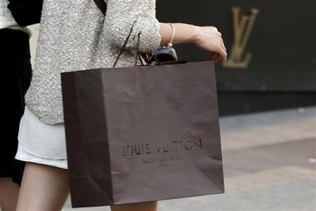 A woman walks with a Louis Vuitton shopping bag as she leaves a Louis Vuitton store in Paris September 24, 2013. REUTERS/Philippe Wojazer