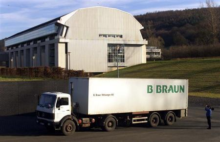 A TV cameraman films a truck of German pharmaceutical factory B.Braun Melsungen AG in front of company headquarters in Melsungen, January 19.