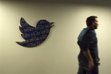 An employee walks past a Twitter logo made from Californian license plates at the company's headquarters in San Francisco, California October 4, 2013. REUTERS/Robert Galbraith