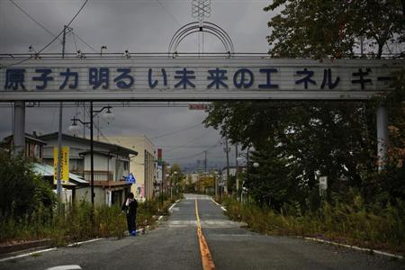 A woman, who came for a brief visit to her home, walks under a sign reading ''Nuclear Power - The Energy for a Better Future'', at the entrance of the empty Futaba town, inside the exclusion zone in Fukushima prefecture September 22, 2013. REUTERS/Damir Sagolj