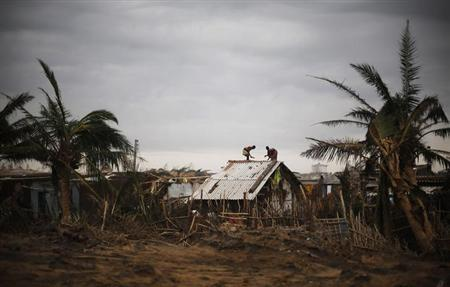 Fishermen and their family members repair the roof of their houses at the cyclone-hit Nalianuagaon village in Ganjam district in Odisha October 15, 2013. REUTERS/Adnan Abidi