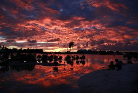 Villagers watch the sunset over a small lagoon near the village of Tangintebu on South Tarawa in the central Pacific island nation of Kiribati May 25, 2013. REUTERS/David Gray