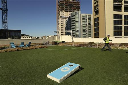 A worker tends to the lawn on the roof of Twitter headquarters in San Francisco, California October 4, 2013. REUTERS/Robert Galbraith
