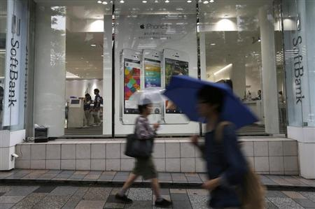 Passersby walk in front of a SoftBank Corp branch in Tokyo June 21, 2013. REUTERS/Issei Kato