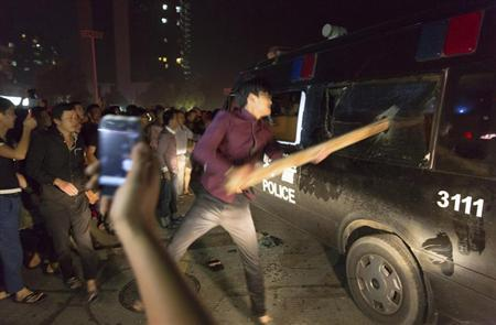 A man breaks the window of a police van with a wooden plank during a protest in Yuyao, Zhejiang province October 11, 2013. REUTERS/Young