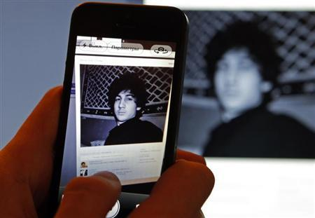 A photograph of Djohar Tsarnaev, who is believed to be Dzhokhar Tsarnaev, a suspect in the Boston Marathon bombing, is seen on his page of Russian social networking site Vkontakte (VK), as pictured on a monitor and a mobile phone in St. Petersburg April 19, 2013. REUTERS/Alexander Demianchuk