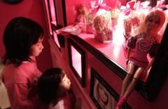 Дети рассматривают кукол Barbie на мероприятии для СМИ по случаю открытия тематического кафе в Тайбэе 30 января 2013 года. Прибыль Mattel Inc за третий квартал превзошла прогнозы Уолл-стрит благодаря хорошему спросу на куклы American Girl и линию игрушек Monster High. REUTERS/Pichi Chuang