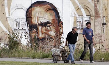 A man pulls a cart filled with pieces of scrap materials for recycling past a pre-election mural, depicting TOP09 political party chairman Karel Schwarzenberg, painted on an abandoned building in Prague October 8, 2013. REUTERS/David W Cerny