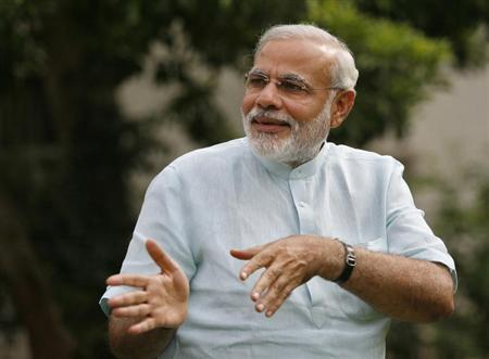Gujarat's Chief Minister Narendra Modi gestures as he walks at the lawns at his residence after an interview with Reuters at Gandhinagar in the western Indian state of Gujarat June 25, 2013. REUTERS/Amit Dave