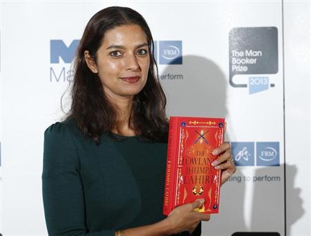 Jhumpa Lahiri poses with her book ''The Lowland'' during a photocall at the Southbank Centre in London, October 13, 2013. REUTERS/Olivia Harris