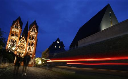 A car drives past the residence of Bishop Franz-Peter Tebartz-van Elst next to Limburg Cathedral (L) in Limburg October 14, 2013. REUTERS/Kai Pfaffenbach
