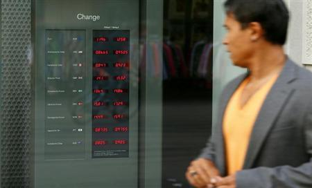A man walks past a display showing the exchange rates of foreign currencies in Zurich October 4, 2013. REUTERS/Arnd Wiegmann