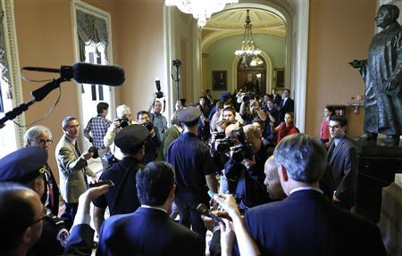 U.S. Senator Ted Cruz (R-TX) (bottom C) is flanked by reporters and police as he departs after a Republican Senate caucus meeting at the U.S. Capitol in Washington, October 16, 2013. REUTERS/Jonathan Ernst