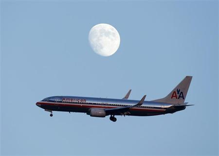 An American Airlines passenger jet glides in under the moon as it lands at LaGuardia airport in New York, August 28, 2012. REUTERS/Eduardo Munoz