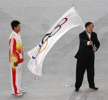 Nanjing Mayor Ji Jianye (R) waves the Olympic flag beside Chinese athlete Gao Tingjie after receiving it from Jacques Rogge (not in picture), President of the International Olympic Committee (IOC), during the closing ceremony of the Singapore 2010 Youth Olympic Games (YOG) at the Marina Bay Floating Platform in Singapore August 26, 2010. REUTERS/Issei Kato