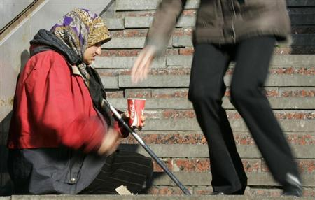 A person drops money into a container of a begging woman in Kiev October 22, 2008. REUTERS/Konstantin Chernichkin