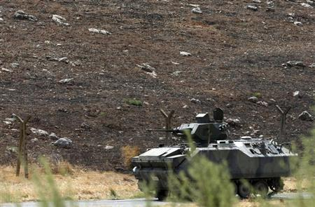 A Turkish military armoured vehicle patrols on the border line near Turkish Cilvegozu border gate, located opposite the Syrian commercial crossing point Bab al-Hawa in Reyhanli, Hatay province, September 17, 2013. REUTERS/Umit Bektas/Files