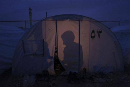 The shadows of Syrian refugees in a tent are seen at Bab al-Salam refugee camp in Azaz, near the Syrian-Turkish border, January 13, 2013. REUTERS/Muzaffar Salman