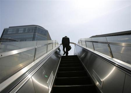 A businessman rides on an escalator in Tokyo's business district April 1, 2013. REUTERS/Toru Hanai