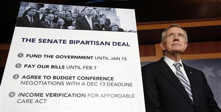 Senate Majority Leader Harry Reid stands beside a placard on the fiscal deal after the Senate voted in the U.S. Capitol in Washington October 16, 2013. REUTERS/Kevin Lamarque