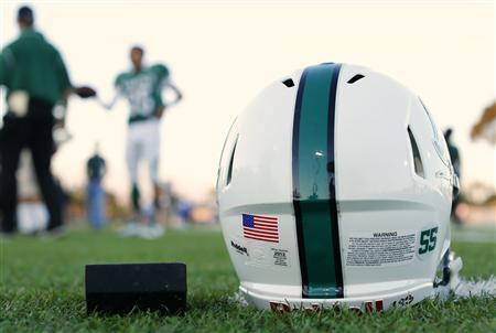 A football helmet's health warning sticker is pictured between a U.S. flag and the number 55, in memory of former student and NFL player Junior Seau, as the Oceanside Pirates high school football team prepares for their Friday night game in Oceanside, California September 14, 2012. REUTERS/Mike Blake