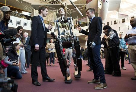 Dr. Bertholt Meyer (R) and James Pope assist the robot ''The Incredible Bionic Man'' while it walks at the Smithsonian National Air and Space Museum in Washington October 17, 2013. REUTERS/Joshua Roberts