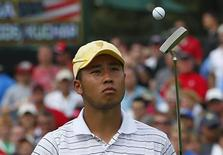 International team player Hideki Matsuyama of Japan flips his ball up after putting on the 14th hole while playing his four ball match with partner Adam Scott of Australia against Tiger Woods and Matt Kuchar of the U.S. at the 2013 Presidents Cup golf tournament at Muirfield Village Golf Club in Dublin, Ohio October 5, 2013. REUTERS/Jeff Haynes