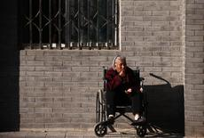 An elderly lady sits in a wheelchair in Beijing, October 16, 2013. REUTERS/Petar Kujundzic