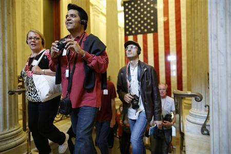 Tourists react as they enter the U.S. Capitol Rotunda on an official visitors' tour, which had been suspended during the 16-day government shutdown, at the U.S. Capitol in Washington, October 17, 2013. REUTERS/Jonathan Ernst