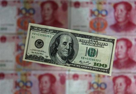 A photo illustration shows a $100 banknote placed above Chinese 100 yuan banknotes in Beijing May 10, 2013. REUTERS/Petar Kujundzic
