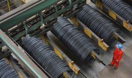 Funcionário de pé perto de bobinas de aço dentro de fábrica em Dalian, na província de Liaoning, China, 18 de outubro de 2013. A economia da China cresceu entre julho e setembro no ritmo mais rápido deste ano, impulsionada pelo investimento, mas analistas se questionam se o ímpeto vai continuar nos próximos meses. 18/10/2013 REUTERS/China Daily