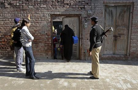 A policeman stands guard as female polio workers wait to give polio vaccine drops to children in Lahore December 20, 2012. REUTERS/Mohsin Raza