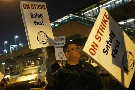Chris Perez, a station agent with Bay Area Rapid Transit (BART), carries a sign while striking outside West Oakland station during morning commute hours in Oakland, California October 18, 2013. REUTERS-Stephen Lam